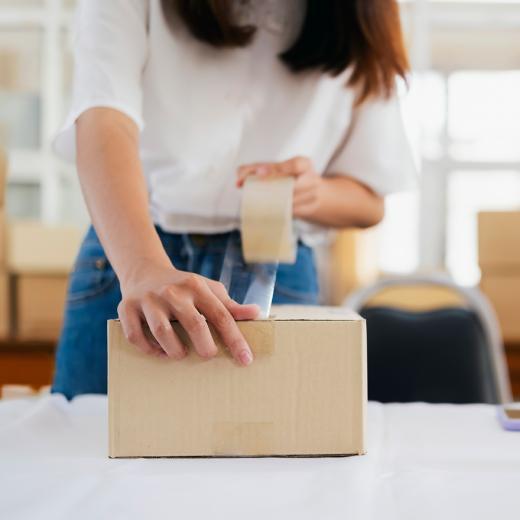 Lady taping carton shut